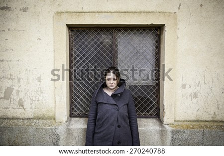 Serious girl in front of building, emotion and feeling - stock photo