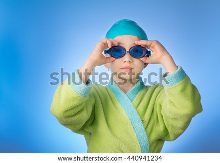 serious girl putting on goggles ready to swim