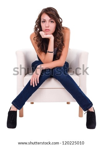 Serious girl sitting in armchair looking to camera - stock photo