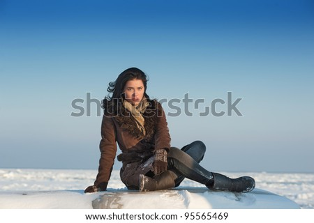 Serious girl sitting on the snow and looking at camera