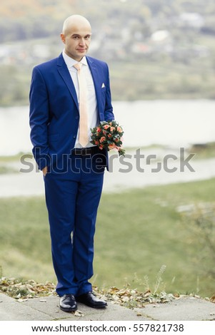Serious groom with wedding bouquet stands on footstep outside