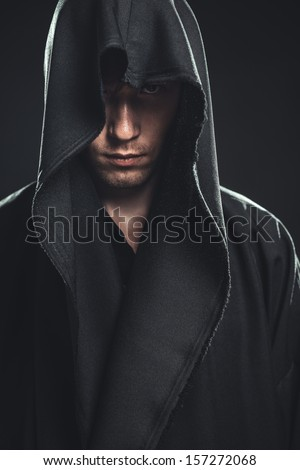 serious guy in a black robe - stock photo