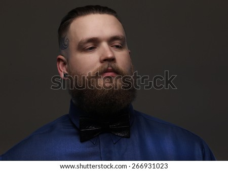 Serious guy in blue shirt and bow tie. Isolated on greyadult,