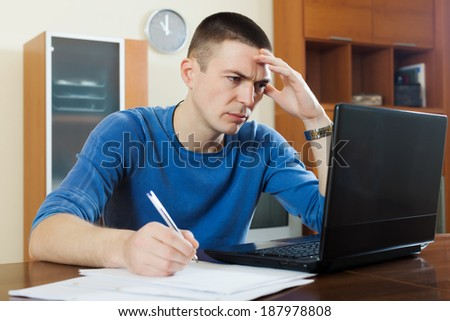 serious guy staring financial documents in laptop  in home