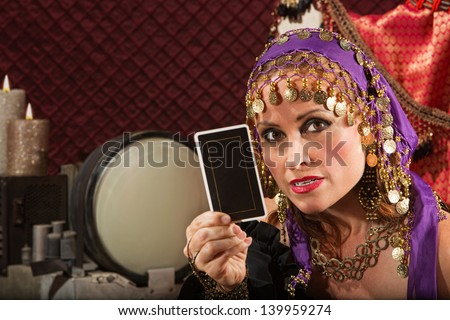 Serious gypsy fortune teller explaining tarot card in her hand - stock photo