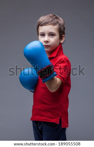 Serious handsome boy posing in boxing gloves