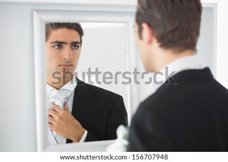 Serious handsome bridegroom looking in mirror straightening his tie  - stock photo