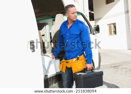 Serious handsome handyman holding toolbox in front of his van - stock photo
