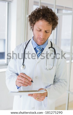 Serious handsome male doctor writing reports in the hospital