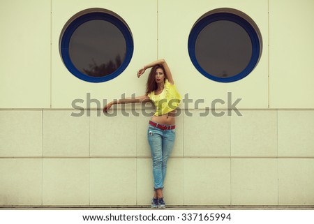 Serious hipster girl dancing in blue jeans in the summer city. Modern youth lifestyle concept. Copy-space. Outdoor shot