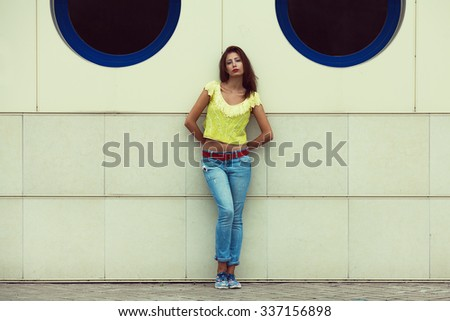 Serious hipster girl in blue jeans in the summer city. Modern youth lifestyle concept. Copy-space. Outdoor shot - stock photo