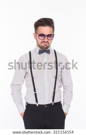 Serious hipster man posing with his hands in pockets in studio. Handsome man in white shirt and sunglasses looking so serious.