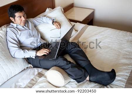 Serious hispanic businessman using laptop in his hotel room - stock photo