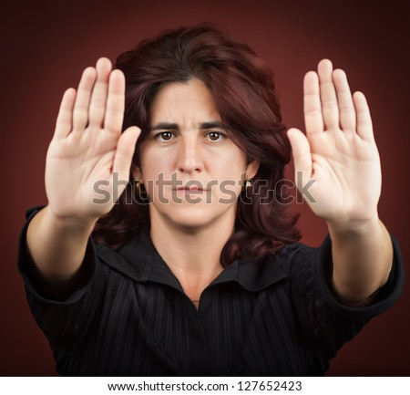 Serious hispanic woman with her two hands extended signaling to stop (useful to campaign against violence or discrimination)