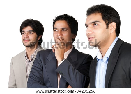 serious Indian business team,serious business team looking and pointing towards left side out of frame - stock photo