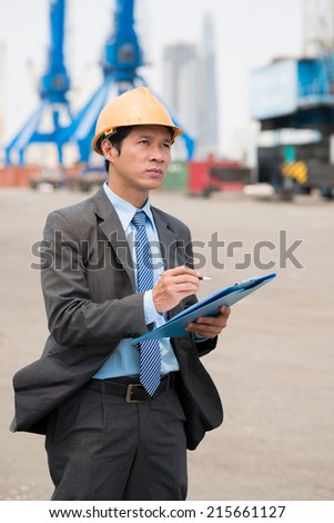 Serious inspector making notes while working at the freight dock