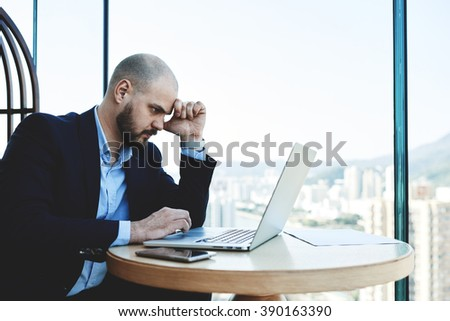 Serious intelligent banker is spending important banking operation via portable laptop computer. Skilled man architect is working on a new project via net-book, while is sitting in office interior - stock photo