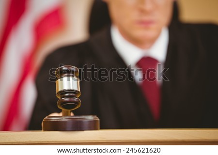 Serious judge about to bang gavel on sounding block in the court room - stock photo