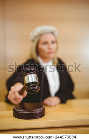 Serious judge with a gavel wearing robes and wig in the court room - stock photo