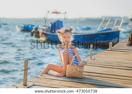 Serious kid girl sitting on a wood pontoon naer the boats at sea