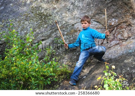 Serious kid with a wooden sword on stone - stock photo