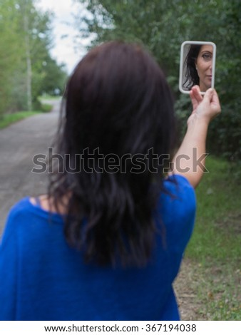 serious lady looking at the mirror - stock photo