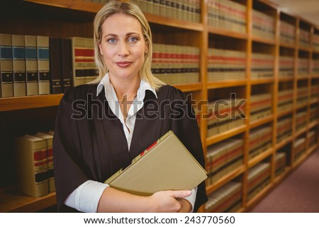 Serious lawyer holding a file while standing in library - stock photo