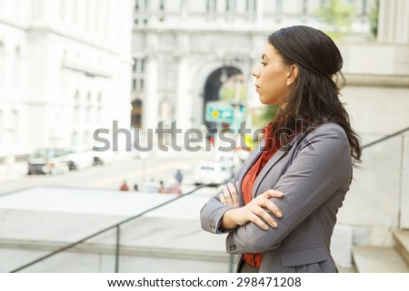 Serious legal or business woman on steps with arms crossed looking forward. - stock photo