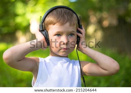 Serious little boy enjoying music in headphones outdoors. - stock photo
