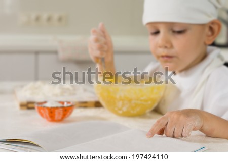 Serious little boy in an apron and white chefs toque reading a recipe book as he bakes in the kitchen - stock photo