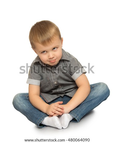 Serious little boy in jeans and a gray shirt. The boy sits on the floor looking up to the sky - Isolated on white background