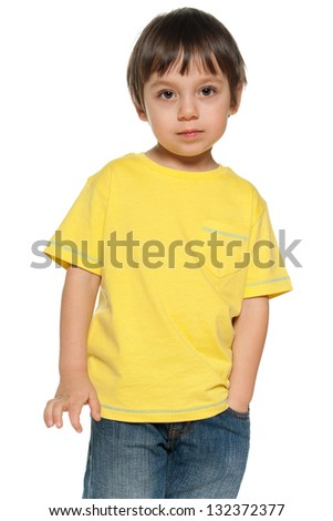 Serious little boy in yellow shirt on the white background