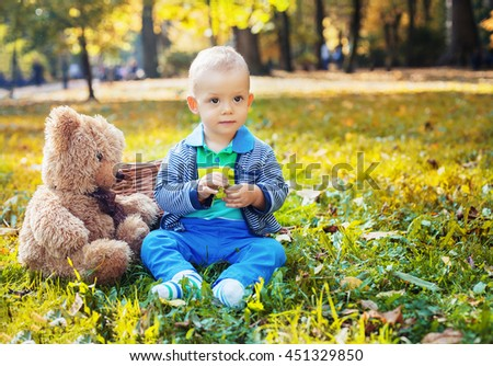 serious little boy is sitting with a bear in the autumn park