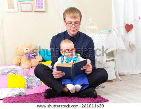 Serious little boy read an old book with his father in glasses - stock photo