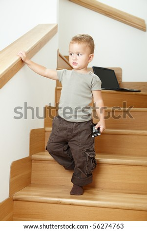 Serious little boy standing on stairs, holding remote control.