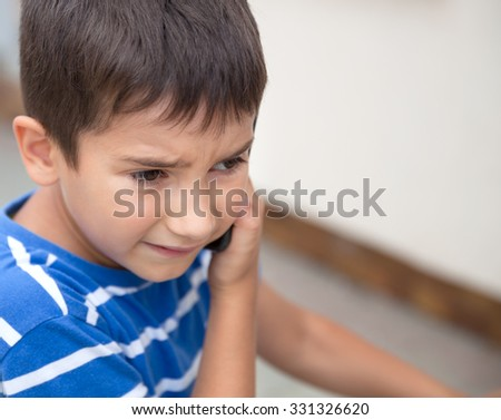 Serious little boy talking on the phone with his parents on light background with copy-space - stock photo