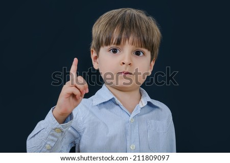 Serious little boy with finger up on a black background