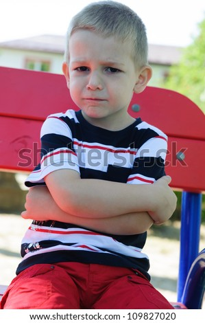 Serious little boy with negative emotions sitting at playground - stock photo