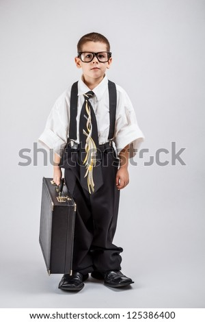 Serious little business boy holding office briefcase - stock photo