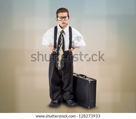 Serious little business boy with office briefcase