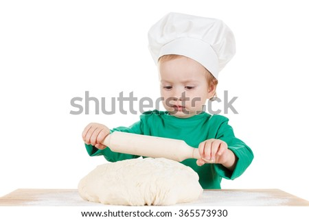 serious little cook boy kneading the dough for the cookies, isolated on white background.  Half-length portrait of the table in studio - stock photo
