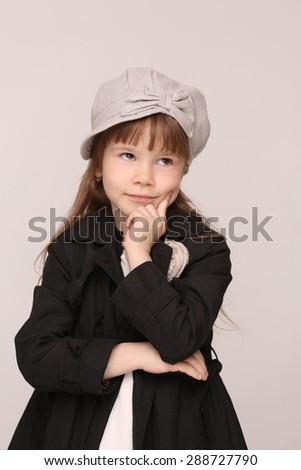 Serious little girl dreaming about boy-friend. Mummy's girl in black coat isolated on white background. - stock photo