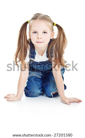 serious little girl in blue jeans sitting on the floor - stock photo