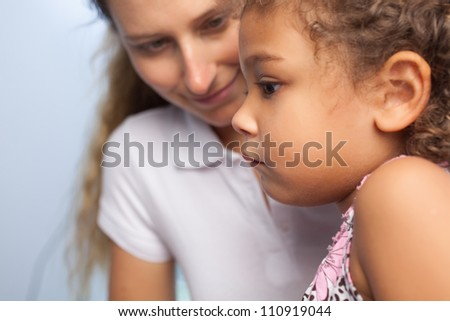 Serious little girl looking at something with her mother on the background - stock photo