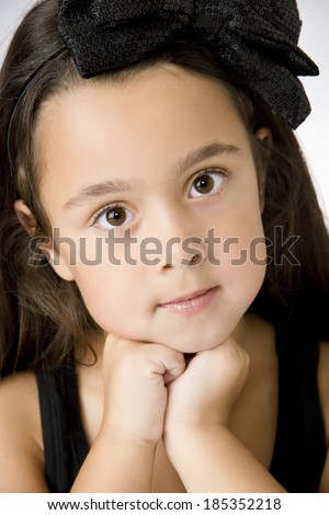 Serious little girl with big eyes resting chin on hands - stock photo