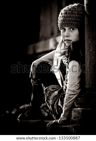 serious little girl with knit hat sitting on ledge looking back, black and white