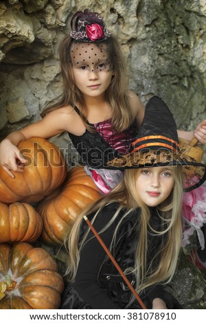 Serious little witches have fun outdoors on Halloween. Trick or  - stock photo