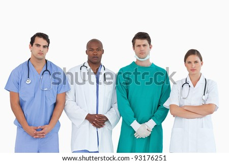 Serious looking medical team standing together against a white background
