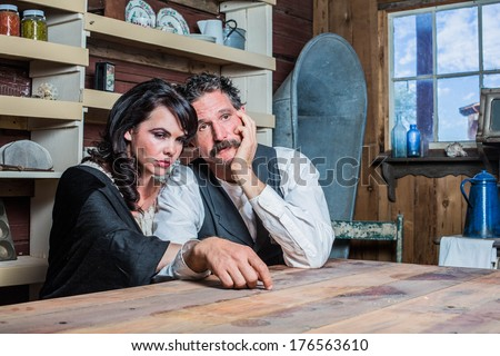 Serious Looking Western Sheriff and Woman Pose Inside of a House - stock photo