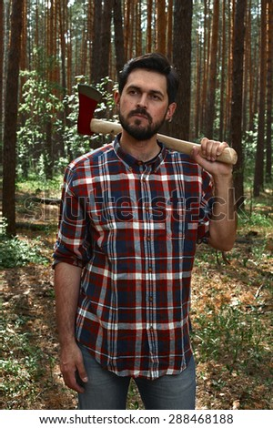 Serious Lumberjack with a big Axe on Shoulder in a Forest - stock photo